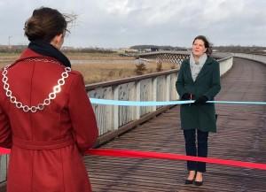 Fleur Gräper-van Koolwijk (gedeputeerde van de provincie Groningen) en Cora-Yfke Sikkema (burgemeester van de gemeente Oldambt) openden de brug met het doorknippen van een lint. © Provincie Groningen.